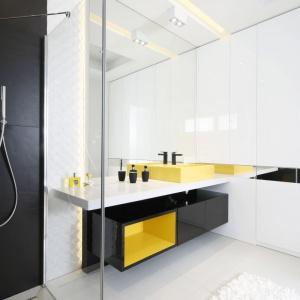 Minimalistyczne wnętrze z żółtymi akcentami pięknie uzupełnia lustrzana tafla. Projekt: Agnieszka Hajdas-Obajtek. Fot. Bartosz Jarosz