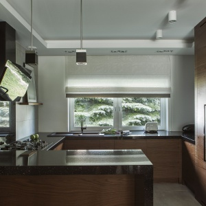 Czarny granit w kuchni tworzy eleganckie połączenie z fornirem orzecha amerykańskiego. Czarne akcesoria, oświetlenie i sprzęty AGD uzupełniają ten wyjściowy garnitur niczym galanteryjne dodatki. Projekt: Anna Nowak-Paziewska, MAFGroup. Zdjęcia i stylizacja: Emi Karpowicz