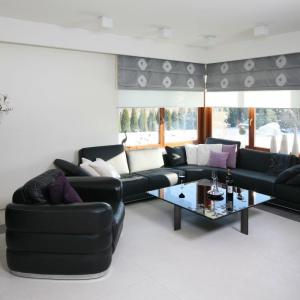 Jednolita powierzchnia podłogi, którą uzyskano dzięki zastosowaniu płytek ceramicznych tworzy estetyczną kompozycję z ciemnymi kanapami. Projekt: Małgorzata Borzyszkowska. Fot. Bartosz Jarosz