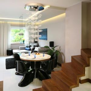 Jasne płytki o dużych formatach znakomicie sprawdzą się w każdym salonie. Tu stanowią doskonałe tło dla czarnych krzeseł i ciemnobrązowych drewnianych schodów. Projekt: Chantal Springer. Fot. Bartosz Jarosz
