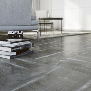 Chłodny szary odcień, matowa, chropowata powierzchnia i nieregularne desenie – podłoga imitująca surowy, przecierany beton, także w salonie będzie prezentować się wyjątkowo. Fot. Cersanit