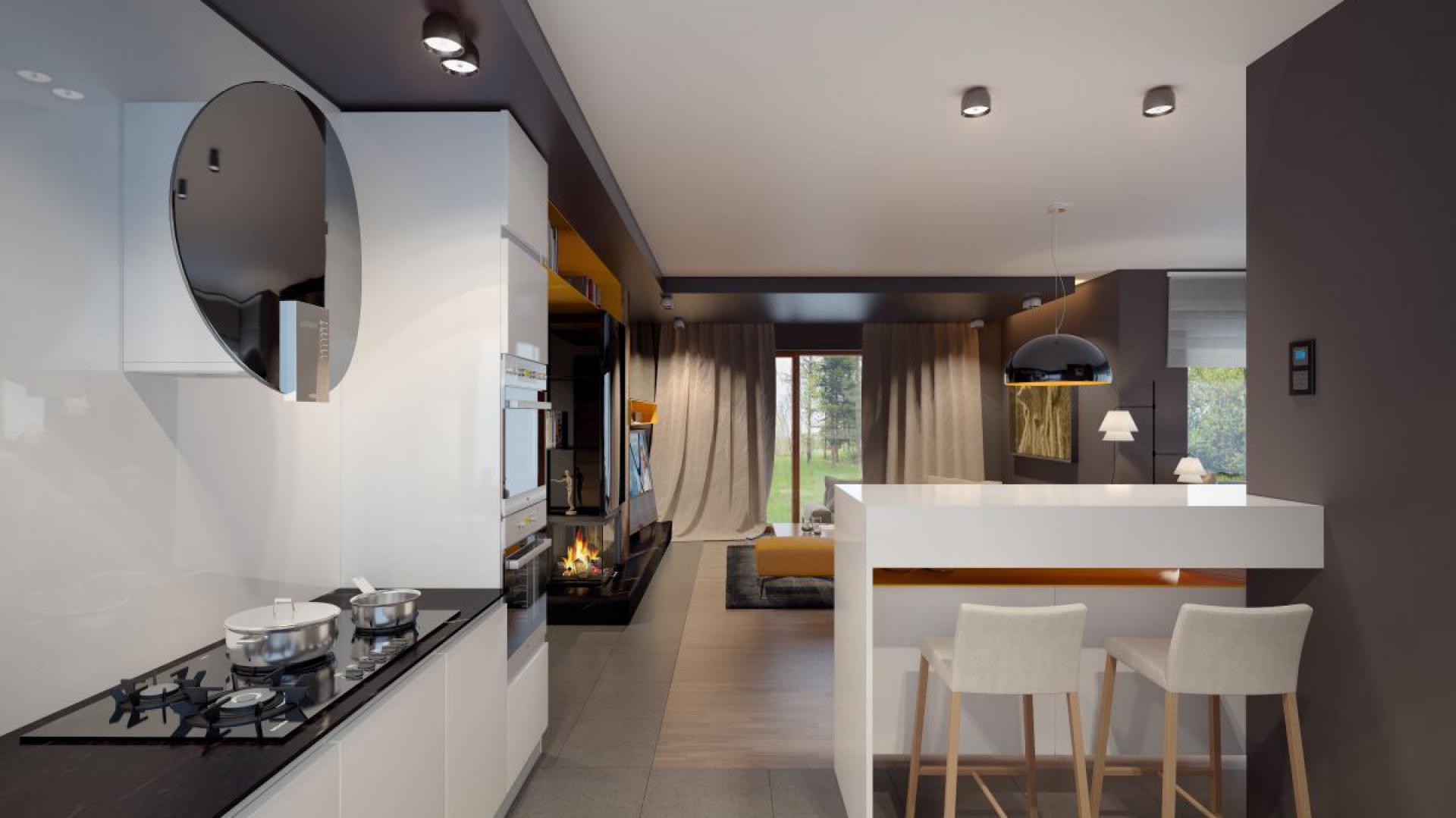 W kuchni króluje biała zabudowa meblowa na wysoki połysk. Bar, który odseparowuje kuchnię od salonu i jadalni jest też miejscem na praktyczny kącik śniadaniowy. Fot. Archetyp