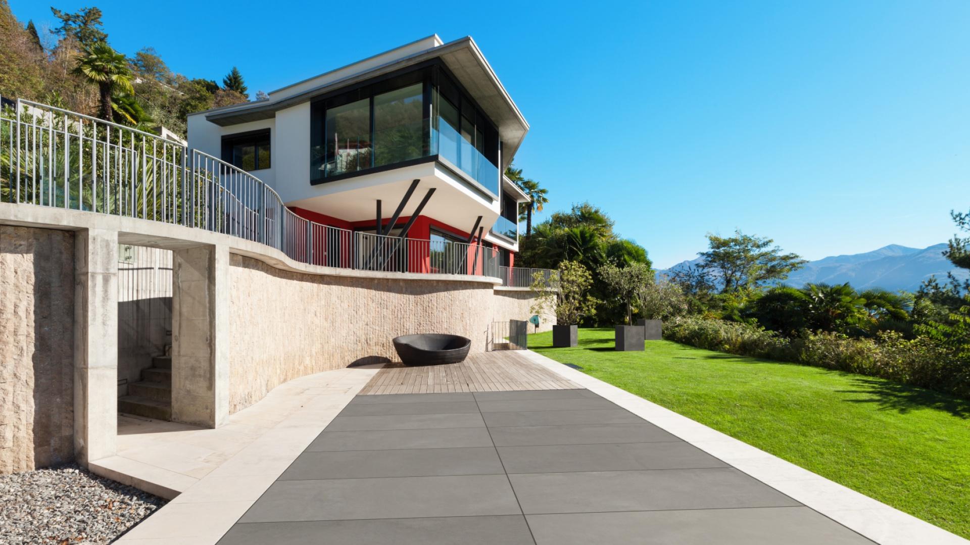 Otwarcie na ogród, brak balustrady i krótko przystrzyżony zielony trawnik w bezpośrednim sąsiedztwie tarasu – to wszystko sprawia, że w nowoczesnych projektach płynnie zanika granica między tarasem a zielonym terenem wokół domu. Betonowe płyty wpisują się w ten krajobraz idealnie. Na zdjęciu: płyta Slim, Modern Line