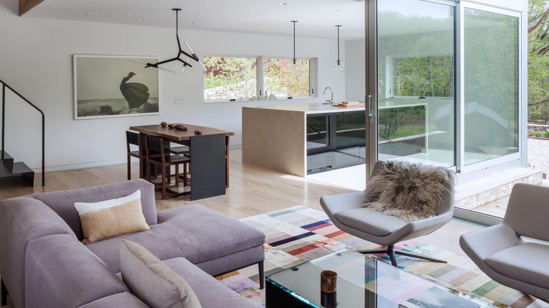Serce domu stanowi otwarta strefa dzienna, w której skład wchodzi elegancki salon urządzony w szarościach, niewielka jadalnia oraz kuchnia z ogromną wyspą. Projekt: Sharon Davis Design. Fot. Elizabeth Felicella