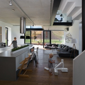 Kształt budynku stwarzał sposobność do zaprojektowania wnętrz o rozległej przestrzeni. Sufit w pomieszczeniach dziennych parteru sięga wysokości 8 metrów. Wielkie okna, które otwierają się na otaczający sielski krajobraz oraz wysokie pokoje z białymi ścianami wypełnione światłem to kwintesencja tego projektu. Projekt: Ola Wołczyk Fot. Hanna Długosz