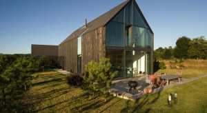 Forma budynku mieszkalnego została utrzymana w charakterze wiejskiego siedliska. Prosty, dwuspadowy dach i elewacje pokryte deskami z modrzewia, spatynowanymi na ciemny kolor, z powodzeniem upodobniły dom do charakterystycznych dawnych wiejskich zabudow