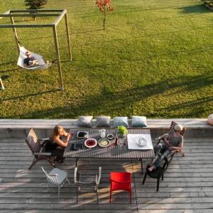 Piękny drewniany taras stylistyką nawiązuje do wykończenia elewacji. Tu toczy się życie towarzyskie podczas ciepłych dni. Projekt: Ola Wołczyk. Fot. Hanna Długosz