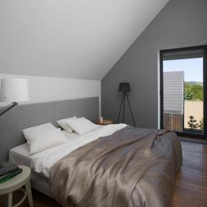 Sypialnia na poddaszu została urządzona zgodnie z minimalistycznymi trendami - w bielach i szarościach. Projekt: Ola Wołczyk. Fot. Hanna Długosz