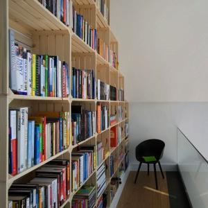 Na antresoli otwartej na przestrzeń parteru znajduje się biblioteka. Oryginalne regały powstały ze specjalnie zamówionych przez inwestorkę skrzynek na owoce. Projekt: Ola Wołczyk. Fot. Hanna Długosz