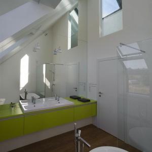Biała łazienka została ożywiona naturalnymi akcentami: zieloną zabudową mebli i drewnem na podłodze. Projekt: Ola Wołczyk. Fot. Hanna Długosz