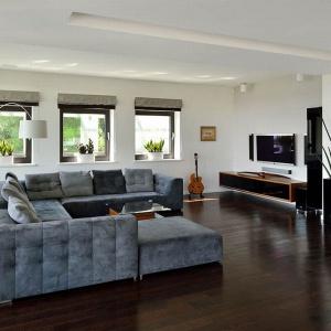 Salon zaprojektowano w minimalistycznym stylu. Białe ściany, szare meble i ciemnoczekoladowa podłoga to kwintesencja tego wnętrza. Projekt: arch. Tadeusz Lemański. Fot. Tomasz Zakrzewski