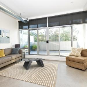Łączenie betonu z różnymi materiałami to skuteczna metoda na ocieplenie jego surowego wizerunku. Tu betonowy stolik Focus w otoczeniu miękkiego dywanu i tapicerowanych mebli