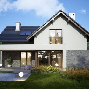 Klasyczna bryła budynku, dzięki zastosowaniu ciekawych materiałów wykończeniowych, jak drewniane panele, czy kamienna okładzina, prezentuje się nowocześnie i elegancko. Szczególnie efektownie wygląda strona ogrodowa - z dużymi przeszkleniami i ciekawym tarasem. Projekt: Ines. Fot. Dobre Domy