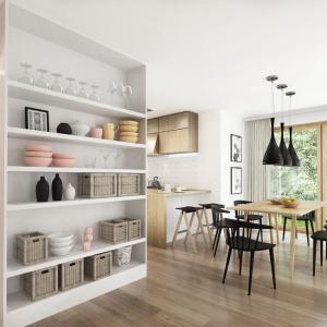 Salon płynnie łączy się z jadalnią i zaprojektowaną nieco na uboczu kuchnią. Dom Aria. Projekt: Marcin Abramowicz, Jagoda Gruca. Fot. Dobre Domy