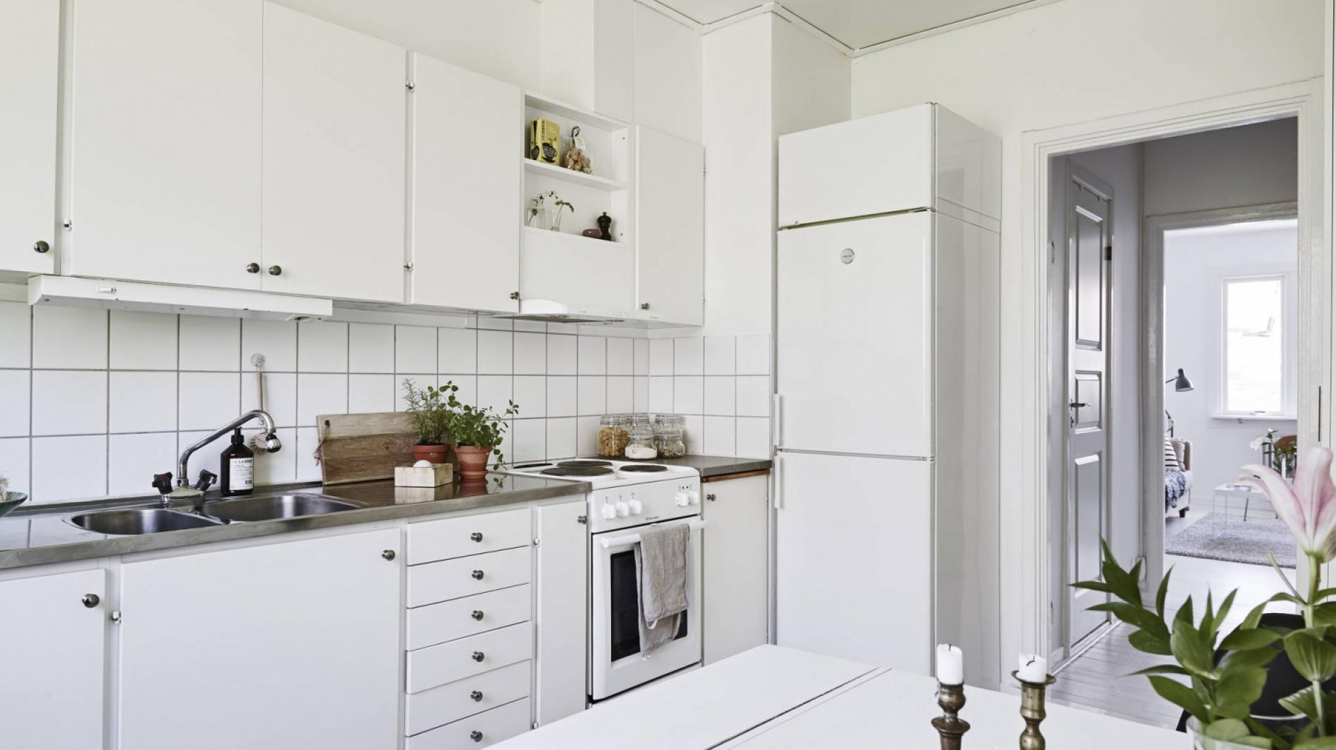 Białe meble kuchenne wieńczy ciemny blat a fronty zdobią okrągłe, czarne uchwyty, wyeksponowane na tle śnieżnobiałych powierzchni. Fot. Stadshem.se/Janne Olander.