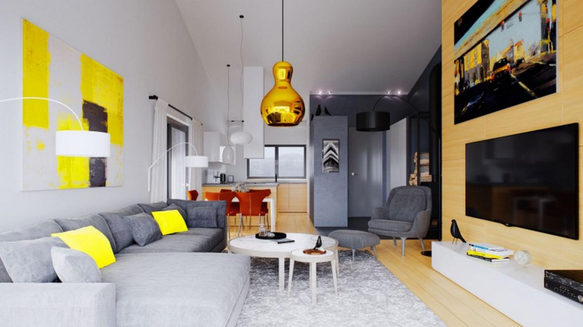 Uwagę zwraca duży rodzinny stół, a także słoneczne dodatki, ożywiające wnętrze swą energetyczną, żółtą barwą. Fot. Archipelag