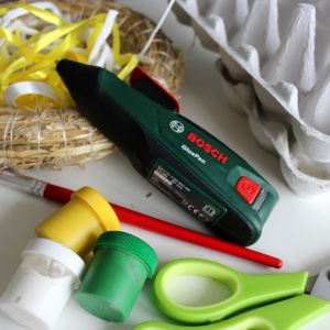 Narzędzia potrzebne do wykonania dekoracji:  papierowe opakowania/ wytłaczanki po jajkach, akumulatorowy pistolet do klejenia Bosch GluePen, podstawa do wianka (z rafii lub styropianu), nożyczki, pędzel, farby plakatowe, rafia, wstążki. Fot. Bosch