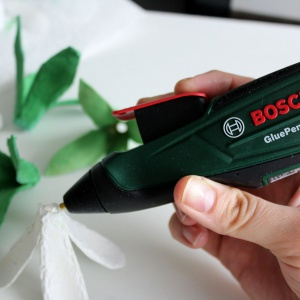 Przy pomocy akumulatorowego pistoletu do klejenia Bosch GluePen łączymy kilka warstw płatków, tworząc wielobarwne kwiaty. Fot. Bosch