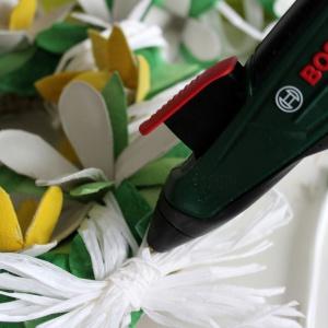 Na koniec dekoracyjnie owijamy wianek rafią, maskując ewentualne prześwity. Jeszcze tylko kokardka (którą też warto przymocować klejem) i wianek skończony! Fot. Bosch