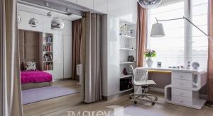 Białe meble na wysoki połysk optycznie powiększają przestrzeń, a beżowe i różowe barwy w dodatkach sprawiają, że aranżacja jest przytulna. W pomieszczeniu przewidziano miejsce na duże lustro ukryte za kotarą, przy którym dziewczynka może tr