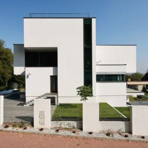 Dom otrzymał formę, nasuwającą skojarzenia z tradycją modernistyczną: ma kubiczne formy i białe elewacje, wycięte w murze pasy okien, pozbawiono go też detalu i ozdobników. Fot. Tomasz Zakrzewski
