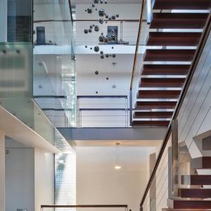 Otwarty charakter wnętrza utrzymano, tworząc ją na różnych poziomach, wykorzystując liczne przeszklenia, które zacierają granice między piętrami. Fot. Tomasz Zakrzewski