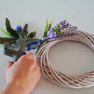 Krok 3 - Do wiklinowego wianka za pomocą pistoletu do klejenia na gorąco Dremel przymocuj sztuczne kwiaty- w pierwszej kolejności te większe (mniejszymi uzupełnisz pozostałe luki). Zdobienie rozplanuj na dolnej połowie wianka, układając kwiaty w dwóch kierunkach.