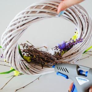 Krok 8 -Gniazdko przyklej z drugiej strony wianka, pod katem 450  tak, aby było widoczne po zawieszaniu wianka na ścianie. Usytuuj je mniej więcej na środku dekoracji z kwiatów.
