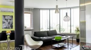 Nowocześnie urządzone mieszkanie na warszawskim Ursynowie. Salon połączony z kuchnią sprawia, że strefa dzienna jest przestronna i bardzo jasna. W aranżacji zastosowano modne odcienie bieli i szarości, jak również kolor limonki, który ożywia w
