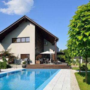Z tyłu domu wybudowano basen, który jest częścią pięknie zaaranżowanego ogrodu.