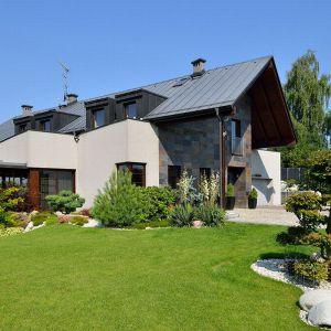 Przesunięcie dachu umożliwiło ukrycie garażu i innych pomieszczeń gospodarczych za domem.