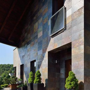 Środkowa cześć fasady została wykończona  płytkami z naturalnego kamienia, które, w zależności od kąta padania promieni słonecznych, mienią się różnymi kolorami - od złocistego, poprzez srebrzysty, aż do brązowego.