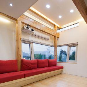 Odkryte części drewnianych konstrukcji bardzo ciekawie ożywiają to minimalistyczne wnętrze.