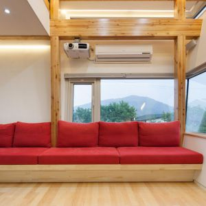 Białe ściany, elementy drewnianej konstrukcji to materiały wykończeniowe dominujące w pomieszczeniach. Zaprojektowano też bardzo funkcjonalne bryły mebli.