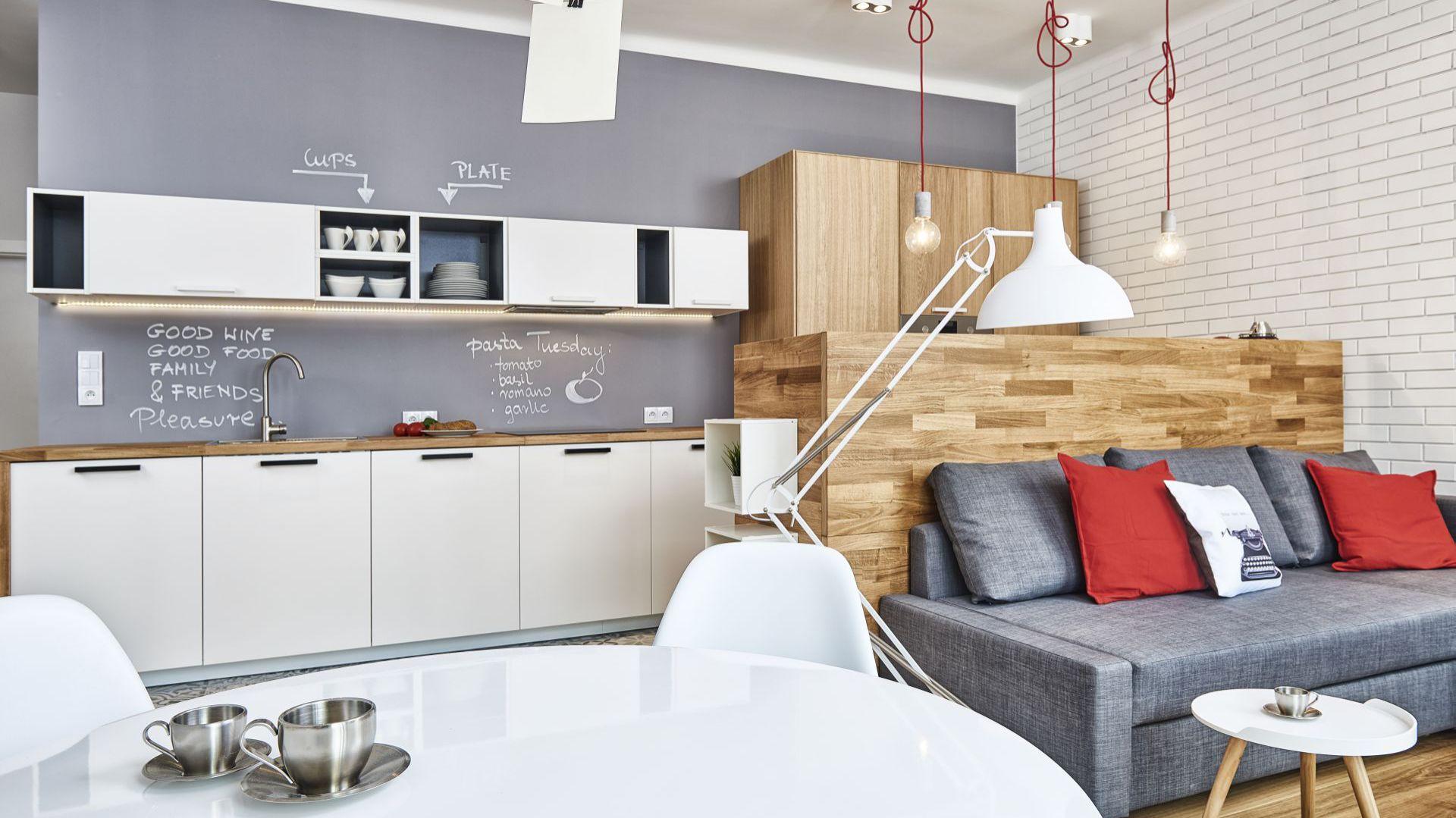 Białe fronty kuchenne optycznie powiększą małą kuchnię. Dodając do nich elementy drewniane sprawimy, że aranżacja będzie przytulna. Projekt Katarzyna Kiełek, Agnieszka Komorowska-Różycka. Fot. Studio 17 pixeli