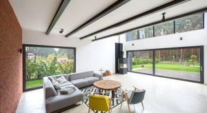Duże okna otwierają dom na ogród i sąsiadujący z nim, wspaniały las. Co więcej, sprawiają, że wnętrze domu przenika się z jego otoczeniem, w którym cisza współgra z przyrodą.