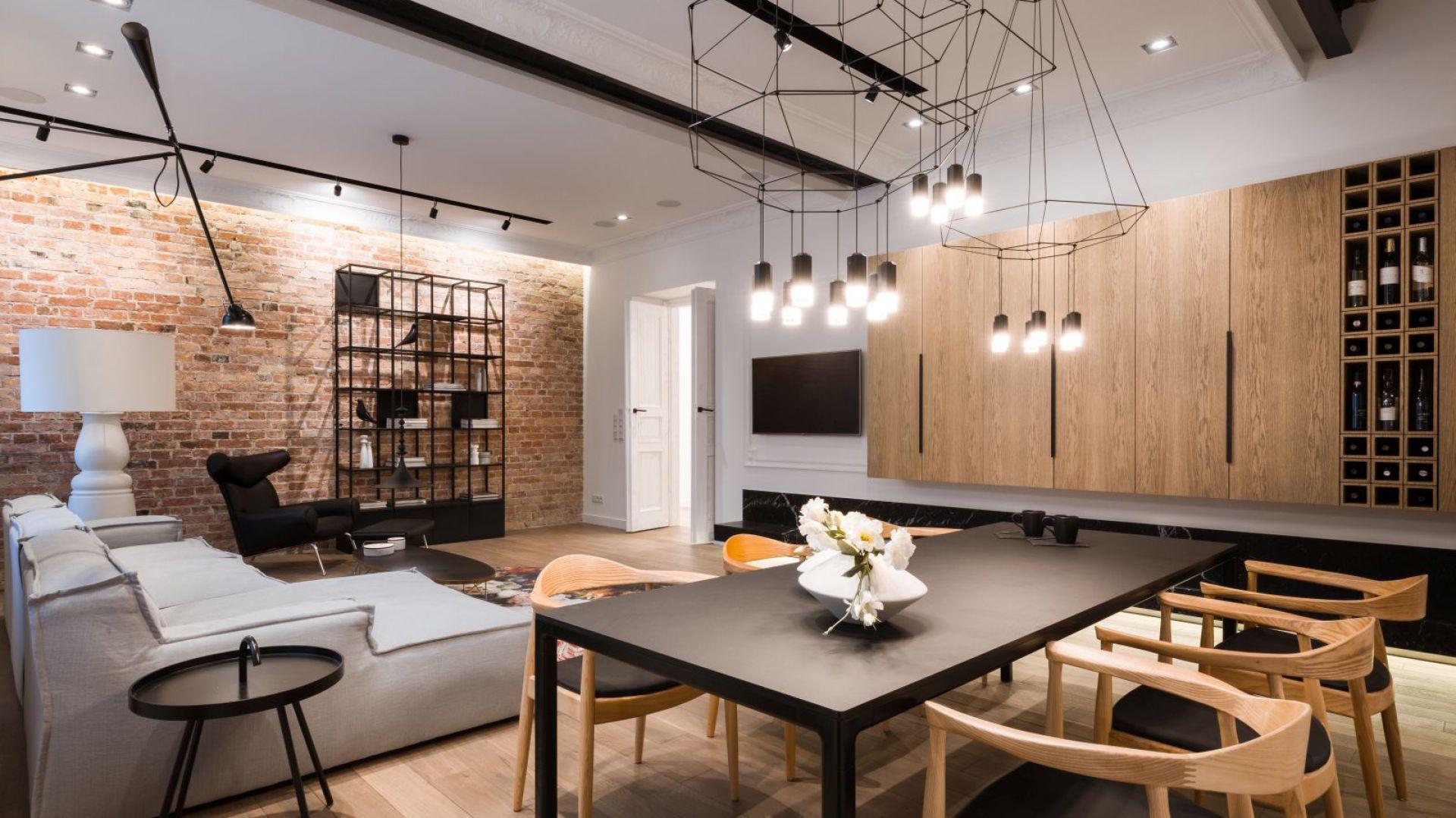 Wnętrze zwraca uwagę finezyjnym połączeniem starego z nowym. Sercem mieszkania jest salon otwarty na kuchnię z jadalnią i strefę wypoczynku. Elementem mającym ogromny wpływ na odbiór przestrzeni jest tu nowoczesne oświetlenie. Zostało tak zaprojektowane, aby precyzyjnie tworzyć sceny świetlne podkreślające klimat mieszkania poprzez wyeksponowanie jego poszczególnych elementów. Fot. Hamish Cox