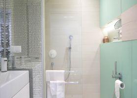 Łazienka z prysznicem, wc z baterią bidetową i wygodna umywalka z szafką. Niewielką przestrzeń ratują płaszczyzny luster, lustrzana mozaika, oraz błyszczące szkło lacobelu. Za taflami lacobelu chowają się spore szafki