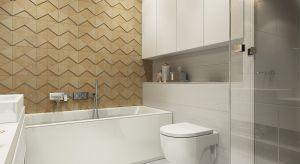 Nowoczesna łazienka została urządzona w jasnych barwach. Całość ociepla ściana w kolorze drewna dodając wnętrzu przytulności.