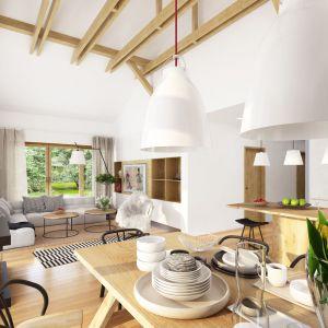 Ciepłe drewno i fragmenty ścian wykończone kamieniem pięknie współgrają z bielą ścian i nowoczesnym oświetleniem. Projekt Hawana. Fot. Dobre Domy