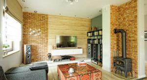 Wnętrze zachowane w ciepłych odcieniach szarości z elementami drewna. Na szczególną uwagę zasługuje lustro w szerokiej drewnianej ramie które optycznie powiększa przedpokój. Naturalne zachowawcze kolory przełamuje czerwona cegła oraz piękna �