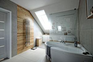 Projekt aranżacji wnętrza domu w Pile o pow.140 m2 Wnętrze zachowane w ciepłych odcieniach szarości z elementami drewna. Na szczególną uwagę zasługuje lustro w szerokiej drewnianej ramie które optycznie powiększa przedpokój. Naturalne zachowawcze kolory przełamuje czerwona cegła oraz piękna ława w marokańskie wzory.