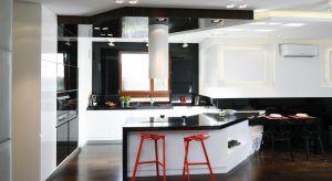 Kuchnia zaaranżowana w czerni i bielijest elegancka i bardzo reprezentacyjna. Stanowi uzupełnienie otwartej strefydziennej, którą urządzono w podobnej tonacjikolorystycznej.