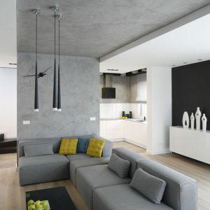 Tu schody ulokowano na uboczy salonu, pod ścianą. Jednak ich ciemny kolor i szklane balustrady dobrze korespondują z minimalistycznym stylem całego wnętrza. Projekt: Łukasz Szadujko. Fot. Bartosz Jarosz