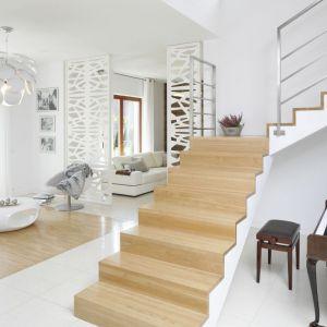Piękne dwubiegowe schody, których stopnie wykończono tym samym gatunkiem drewna, co podłogę w salonie. Ich słomkowy kolor przepięknie komponuje się z białym wnętrzem. Projekt: Agnieszka Ludwinowska. Fot. Bartosz Jarosz
