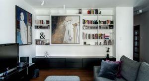 Niewielkie mieszkanie zostało urządzone w nowoczesnym stylu. Wnętrza ocieplono ciepłymi barwami, wystrojowi artystycznego sznytu dodają obrazy zawieszone w salonie.