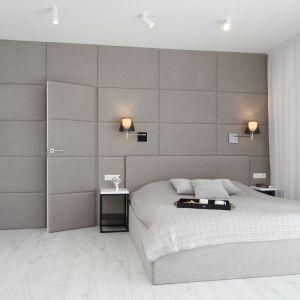 Aranżacja ściany za łóżkiem - tapicerowany, miękki materiał rozciągnięto nawet na drzwi, co daje niezwykle elegancki i przytulny efekt. Projekt: Ewelina Pik, Maria Biegańska. Fot. Bartosz Jarosz