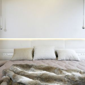 W ścianę za łóżkiem wykończoną zagłówkiem wkomponowano ciekawe oświetlenie. Projekt: Agnieszka Hajdas-Obajtek. Fot. Bartosz Jarosz