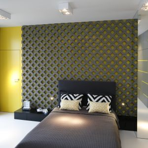 Ścianę za łóżkiem można wykończyć ciekawymi panelami - tu szare, ażurowe struktury imitujące beton pięknie komponują się z żółta farbą. Projekt: Monika i Adam Bronikowscy. Fot. Bartosz Jarosz