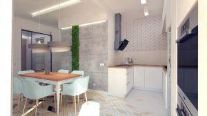 Kuchnia jest jasna i otwarta na salon. Motyw jodełki powtarza się na ścianie jako subtelna geometria. Mech jest przyjemnym kontrastem dla betonowej ściany, a dodatkowo nawiązuje do widoku za oknem - lasu.